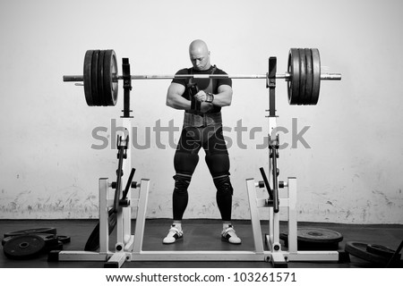 Powerlifter with strong arms preparing to lift a heavy dumbbell - stock photo