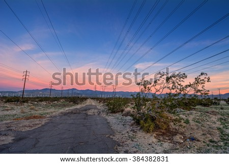 Powerlines above, desolate roads leading to the mountain, sun creates pink sky - stock photo