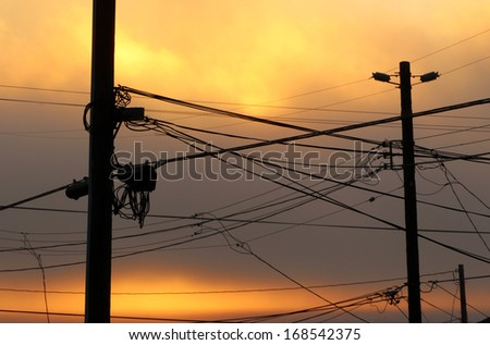 Powerlines with colored clouds and sunset
