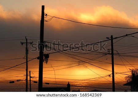 Powerlines with Sun in Fog  - stock photo