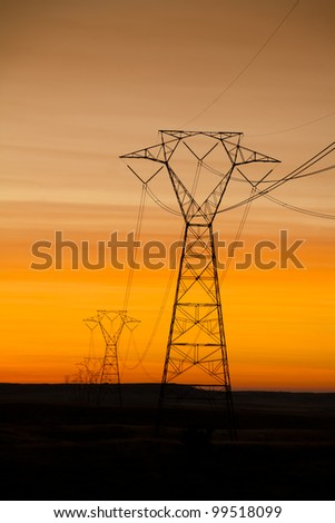 Powerlinge over a beautiful orange sunset - stock photo