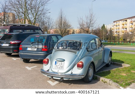 POZNAN, POLAND - APRIL 03, 2016: Parked classic Volkswagen beetle on a parking lot close by apartment buildings - stock photo