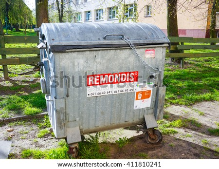 POZNAN, POLAND - APRIL 25, 2016: Remondis trash container locked with a chain at a park on a sunny day