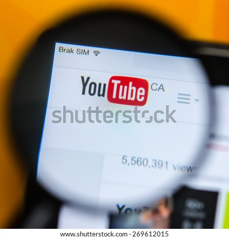 Poznan, Poland - April 15, 2015: YouTube CA website home page on Ipad display  - seen through magnifying glass (loupe) YouTube is the popular online video-sharing website, founded in February 14, 2005 - stock photo
