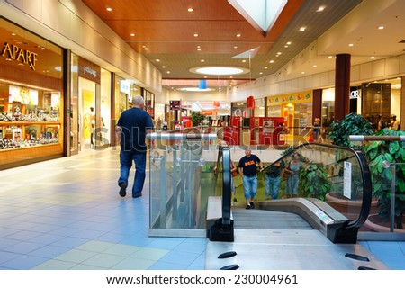 POZNAN, POLAND - AUGUST 10, 2013: People using a escalator at the shopping mall King Cross - stock photo