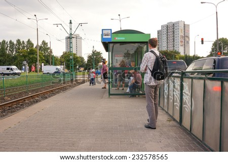 POZNAN, POLAND - AUGUST 22, 2013: People waiting at a bus stop in the Jana Pawla II street in Poznan, Poland - stock photo