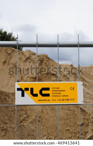 POZNAN, POLAND - AUGUST 13, 2016: TLC construction company board on a metal fence in front of a construction area