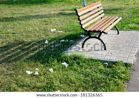 POZNAN, POLAND - AUGUST 17, 2013: Trash on the grass around a wooden bench