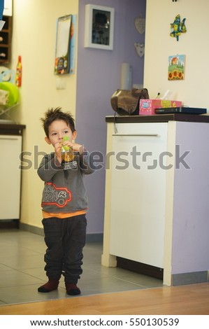 POZNAN, POLAND - DECEMBER 03, 2016: Unidentified two years old boy drinking Kubus juice from a plastic bottle in a room