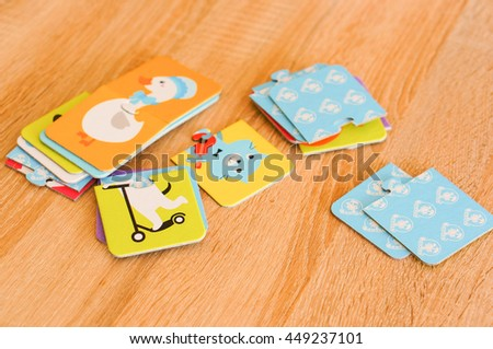 POZNAN, POLAND - FEBRUARY 28, 2016: Child playing puzzles with animal illustrations lying on wooden background