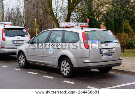 POZNAN, POLAND - JANUARY 25, 2015: Taxi car parked by a sidewalk - stock photo