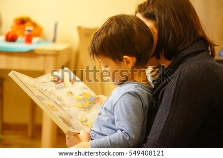 POZNAN, POLAND - JANUARY 05, 2017: Unidentified woman reading to two years old boy a polish book about cars on a sofa