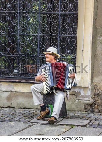 POZNAN, POLAND - JULY 25, 2014: A street musician at the old market of Posen, Poland. The market is from the  the 16th century. - stock photo