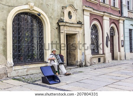 POZNAN, POLAND - JULY 25, 2014: A street musician at the old market of Poznan, Poland. The market is from the  the 16th century. - stock photo