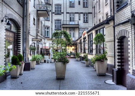 POZNAN, POLAND - JUNE 28, 2014: Picturesque yard in an old house, between the streets Wozna and Wielka. In the yard there are numerous cafes and restaurants.  - stock photo