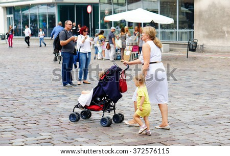 POZNAN, POLAND - JUNE 13, 2013: Woman walking with buggy and holding hand of a girl on the city square - stock photo