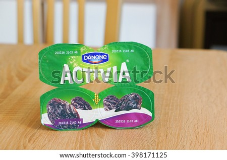 POZNAN, POLAND - MARCH 18, 2016: Four pack of Danone Activia yogurt with dry plums on wooden background - stock photo