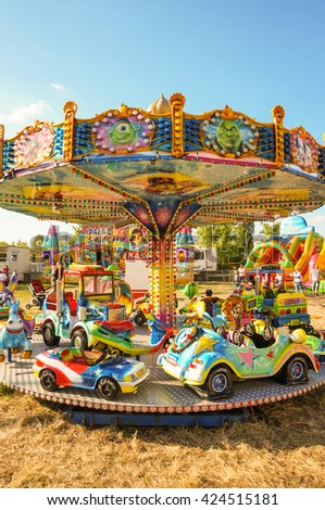 POZNAN, POLAND - MAY 14, 2016: Carousel with different vehicles for kids on a fair ground on a very sunny day - stock photo
