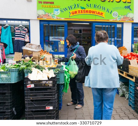 POZNAN, POLAND - MAY 29, 2014: People doing shopping at a vegetables store - stock photo