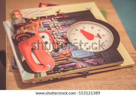 POZNAN, POLAND - NOVEMBER 19, 2016: Disney Cars cartoon child book lying on wooden table in soft focus