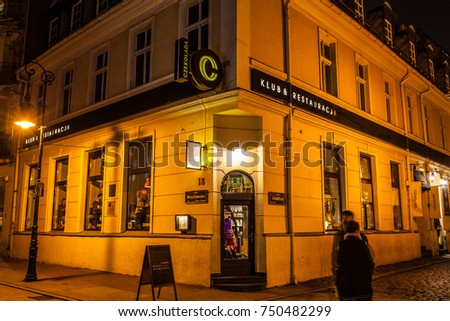 Poznan, Poland, November 04, 2017: old Market Square at night, Chocolate Club, restaurant, cuisine, Czekolada Klub Restauracja on the corner of Wroclawska and Jaskolcza Streets
