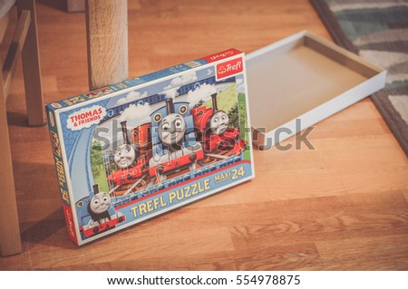 POZNAN, POLAND - NOVEMBER 06, 2016: Thomas and Friends opened puzzle box lying next to a table indoor