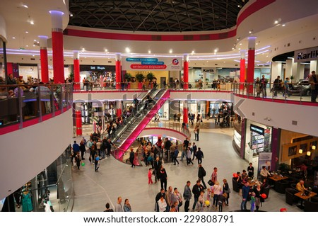 POZNAN, POLAND - OCTOBER 26, 2013: People using the escalator and the busy shopping mall Poznan City Center - stock photo