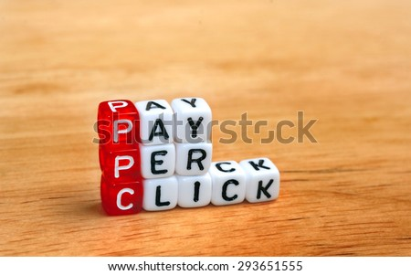 PPC Pay Per Click text on  dices on wooden background - stock photo