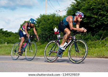 PRACHUABKIRIKHAN, THAILAND - AUGUST 7: Unidentified men cycle during triathlon event near a mountain on August 7,2011 in Prachuabkirikhan, Thailand. - stock photo