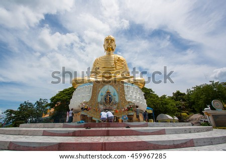 Prachuap Khiri Khan, Thailand: July 19.2016 People pray for blessings with a golden Buddha on the hill facing the sea in Prachuap Khiri Khan, Thailand.