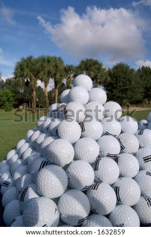 practice golf balls are stacked in pyramid at driving range