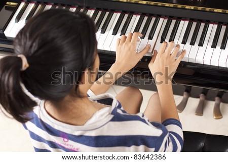 practice piano, asian teenage girl practicing piano. - stock photo