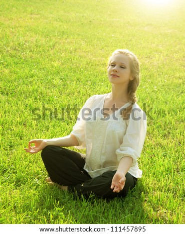 practice yoga outdoors. young woman sitting in the lotus position on the grass in nature - stock photo