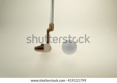 Practicing putter. Golf club and ball.