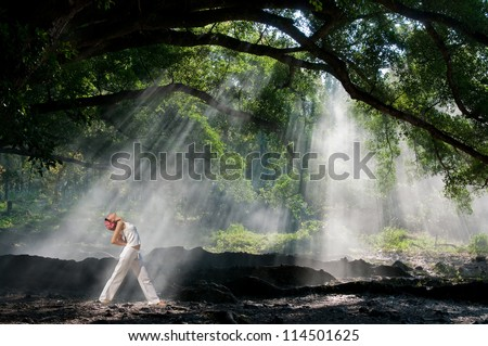Practicing yoga in the morning, with trees and sun ray in the background - stock photo