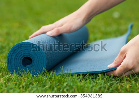 Practicing yoga or pilates outdoors. revive and restore your concentration, energy by doing few stretches in park. Soft focus image of preparation for yoga brake.