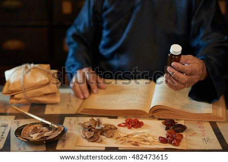 Practitioner of Asian traditional medicine giving medicine he prepared
