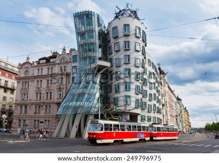 PRAGUE - AUGUST 20: Dancing House with passing tram on August 20, 2014 in Prague. The Dancing Housewas designed 1992 by Vlado Milunic and Frank Gehry and completed 1996  - stock photo