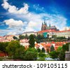 Prague castle among buildings with red roofs and green gardens - stock photo