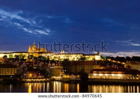 Prague Castle at night with reflections in the river - stock photo