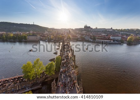 Prague, Charles Bridge from above, Vltava River, Prague Castle. The historic center of Prague at sunset in the spring. Soft light. People walking on the Charles Bridge. Romance in Prague - stock photo