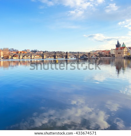 Prague, Charles bridge reflected in Vltava river in the morning, vertical panorama, space for your text