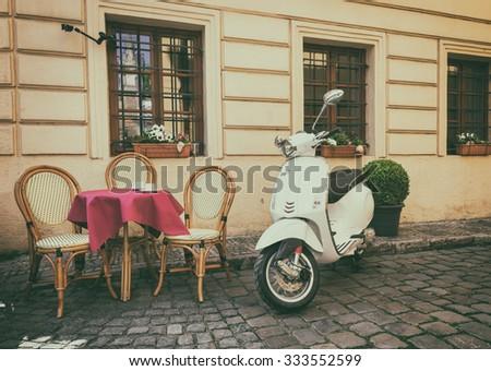 PRAGUE, CZECH REPABLIC - APRIL 22, 2015: Old Vespa parked near cafe in Prague, Czech Republic - stock photo