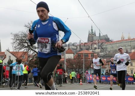 PRAGUE, CZECH REPUBLIC - APRIL 6, 2013: Athletes run in front of Prague Castle with St Vitus Cathedral during the Prague international marathon in Prague, Czech Republic. - stock photo