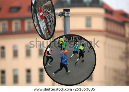 PRAGUE, CZECH REPUBLIC - APRIL 6, 2013: Convex mirrors with the reflection of athletes running a marathon run in Prague, Czech Republic. - stock photo