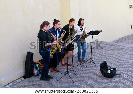 Prague, Czech Republic - April 23, 2015: Group of young girls musicians with saxophones in the city streets - stock photo