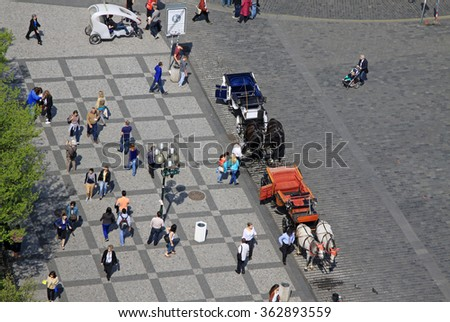 PRAGUE, CZECH REPUBLIC - APRIL 24, 2013:  People walking and horse carriages waiting for tourists at the Old Square