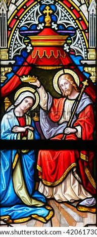 PRAGUE, CZECH REPUBLIC - APRIL 5, 2016: Stained Glass in the Basilica of Vysehrad in Prague, Czech Republic, depicting Christ placing a crown on the head of Mary as Queen of Heaven - stock photo