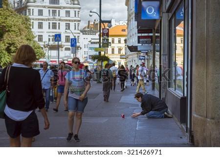 PRAGUE, CZECH REPUBLIC - AUGUST 25, 2015: A homeless beggar is begging on a busy street in the center of Prague, Czech Republic - stock photo