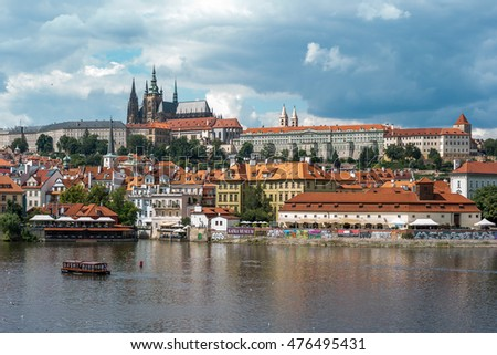 Prague, Czech Republic - August 11, 2016: central Prague photographed on a sunny cloudy day, with the Prague Castle in the background and the Kafka Museum in the foreground.